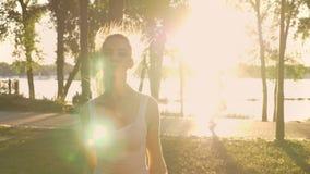 Jovem mulher que faz o exercício no parque, perda da estrela de peso, salto modelo da aptidão, a outra mulher que corre sobre a p vídeos de arquivo