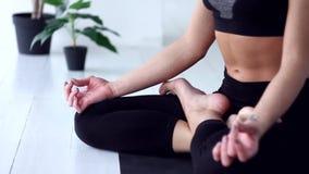Jovem mulher que faz o exerc?cio da ioga em casa video estoque