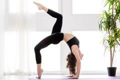 Jovem mulher que faz o exerc?cio da ioga em casa fotografia de stock