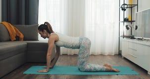 Jovem mulher que faz o exerc?cio em casa Menina da aptidão que faz exercícios da ioga na esteira Estilo de vida saud?vel e do esp video estoque