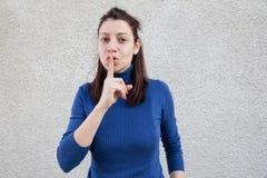 Jovem mulher que faz o sinal do silêncio Fotos de Stock