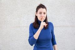 Jovem mulher que faz o sinal do silêncio Fotografia de Stock