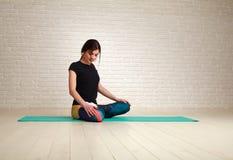 Jovem mulher que faz os exercícios da ioga que sentam-se na pose dos lótus Fotografia de Stock