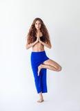 Jovem mulher que faz a pose da árvore do exercício da ioga fotografia de stock royalty free
