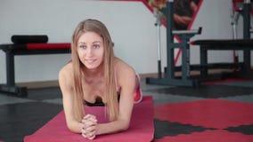 Jovem mulher que faz a prancha do exercício no gym A menina estica os músculos da imprensa abdominal vídeos de arquivo