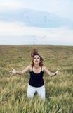 Jovem mulher que faz saltos loucos em um campo de trigo Imagens de Stock Royalty Free