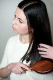 Jovem mulher que faz seu cabelo escuro bonito Fotografia de Stock
