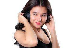 Jovem mulher que faz um bWoman que escuta a música nos fones de ouvido que apreciam uma onda do musicicep isolada no whit Foto de Stock