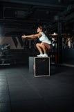 Jovem mulher que faz um exercício do salto da caixa foto de stock