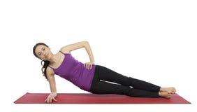 Jovem mulher que faz uma variação da pose lateral da prancha Foto de Stock