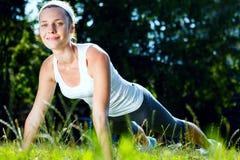 A jovem mulher que fazer empurra levanta no verde Fotografia de Stock