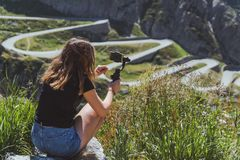 Jovem mulher que filma a estrada do tremola no gotthard de san usando um smartphone e uma suspensão Cardan fotos de stock royalty free