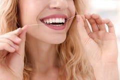Jovem mulher que flossing seus dentes, imagens de stock