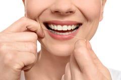 Jovem mulher que flossing seus dentes no fundo branco imagens de stock royalty free