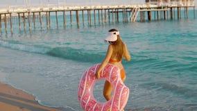 Jovem mulher que flutua com uma filhós inflável, verso video estoque