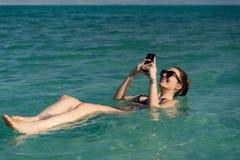 Jovem mulher que flutua na superfície da água do Mar Morto e que usa seu smartphone fotos de stock royalty free