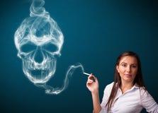 Jovem mulher que fuma o cigarro perigoso com fumo tóxico do crânio Foto de Stock