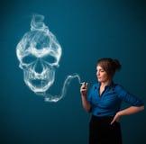 Jovem mulher que fuma o cigarro perigoso com fumo tóxico do crânio Imagens de Stock Royalty Free