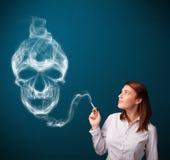 Jovem mulher que fuma o cigarro perigoso com fumo tóxico do crânio Fotografia de Stock Royalty Free