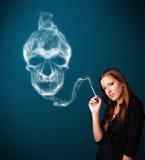Jovem mulher que fuma o cigarro perigoso com fumo tóxico do crânio Fotos de Stock Royalty Free