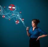 Jovem mulher que fuma o cigarro perigoso com sinais não fumadores Fotos de Stock Royalty Free