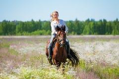 Jovem mulher que galopa horseback no prado florido Foto de Stock Royalty Free