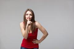 Jovem mulher que gesticula para quieto ou que cala sobre o fundo cinzento Imagens de Stock Royalty Free