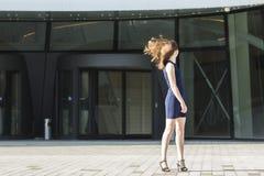 Jovem mulher que gira seu cabelo de ondulação da cabeça, estando no fundo do centro de negócios Fotos de Stock