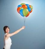 Jovem mulher que guarda balões coloridos Fotos de Stock Royalty Free