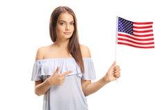 Jovem mulher que guarda a bandeira de América e de apontar imagens de stock