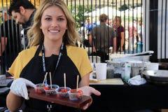 Jovem mulher que guarda a bandeja com oferecimento de amostras de alimento, festival do alimento de Encinitas, San Diego Californ Fotografia de Stock Royalty Free
