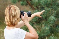 Jovem mulher que guarda a câmara digital e que toma imagens Fotografia de Stock