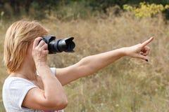 Jovem mulher que guarda a câmara digital e que toma imagens Imagens de Stock Royalty Free