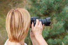 Jovem mulher que guarda a câmara digital e que toma imagens Fotos de Stock