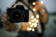 Jovem mulher que guarda a câmera digital da foto com luz do bokeh fotos de stock royalty free