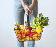 Jovem mulher que guarda a cesta vegetal imagens de stock royalty free