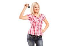 Jovem mulher que guarda a chave do carro Imagens de Stock