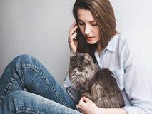 Jovem mulher que guarda delicadamente um gatinho fotografia de stock royalty free