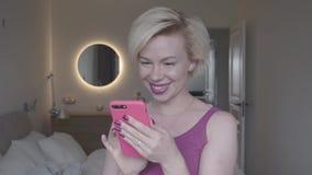 Jovem mulher que guarda e que usa seu smartphone, sorriso e datilografia Movimento lento filme