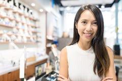 Jovem mulher que guarda a empresa de pequeno porte na loja do ótico fotografia de stock