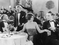 A jovem mulher que guarda a mão de um homem em uma tabela diferente quando seu companheiro falar ao garçom (todas as pessoas desc imagem de stock