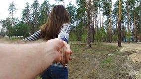 Jovem mulher que guarda a mão do homem e que conduz o na natureza exterior video estoque