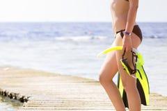 Jovem mulher que guarda mergulhar a engrenagem que olha o mar Foto de Stock