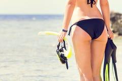 Jovem mulher que guarda mergulhar a engrenagem que olha o mar Imagens de Stock Royalty Free