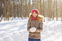 Jovem mulher que guarda a neve branca macia natural em suas mãos para fazer uma bola de neve, sorrindo durante um dia de inverno  Imagem de Stock