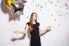 Jovem mulher que guarda o balão da estrela com confetes da mosca no partido imagem de stock royalty free
