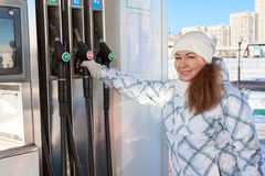 Jovem mulher que guarda o bocal de abastecimento na estação do petróleo Imagens de Stock