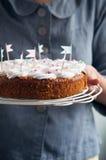 Jovem mulher que guarda o bolo de cenoura Imagem de Stock