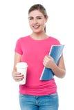 Jovem mulher que guarda o copo do caderno e da bebida Imagens de Stock Royalty Free