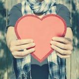 Jovem mulher que guarda o coração vermelho grande em suas mãos Imagens de Stock
